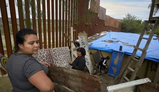 In this Jan. 16, 2019, image, Yuli Arias, left, stands near a newly-replaced section of the border wall as her mother, Esther Arias, center, stands in the family's house that was once threatened by construction along the border in Tijuana, Mexico. The U.S. faces a delicate dance as it charts a course to extend or replace border barriers near homes and structures. (AP Photo/Gregory Bull)