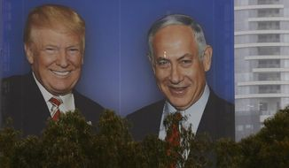 """In this Wednesday, Feb. 6, 2019 photo, an election campaign billboard shows Israeli Prime Minister Benjamin Netanyahu, and US President Donald Trump in Tel Aviv, Israel. Seeking re-election under a cloud of criminal investigations, Israeli Prime Minister Benjamin Netanyahu is apparently channeling his inner Donald Trump in an angry campaign against perceived domestic enemies. Drawing clear inspiration from Trump, Netanyahu's Likud party has plastered huge billboards of the two leaders together and launched a Trump-like weekly webcast to counter what it calls the """"fake news"""" industry. (AP Photo/Ariel Schalit)"""