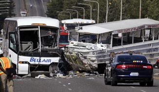 """FILE - In this Sept. 24, 2015, file photo, a """"Ride the Ducks"""" amphibious tour bus, right, and a charter bus remain at the scene of a multiple fatality collision on the Aurora Bridge in Seattle. A jury has awarded about $123 million to victims and families in a 2015 duck boat crash that killed five college students and wounded more than 60 others in Seattle. The Seattle Times reports Thursday, Feb. 7, 2019 that King County Superior Court jurors after a four-month civil trial found that Ride the Ducks International bore 67 percent of the responsibility for the crash, and tour vehicle operator Ride The Ducks of Seattle was 33 percent at fault. (AP Photo/Elaine Thompson, File)"""
