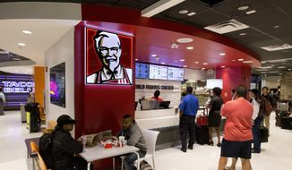 In this Oct. 17, 2017, file photo, customers line up at a Kentucky Fried Chicken restaurant inside Miami International Airport in Miami. (AP Photo/Wilfredo Lee, File)