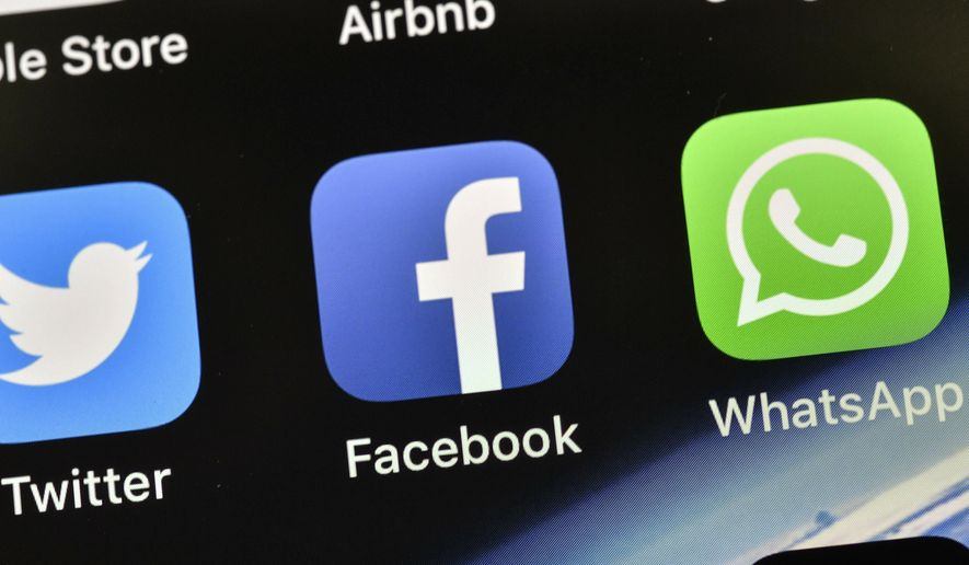 In this Thursday, Nov. 15, 2018 file photo the icons of Facebook and WhatsApp are pictured on an iPhone in Gelsenkirchen, Germany. (AP Photo/Martin Meissner)