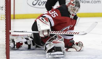 New Jersey Devils goaltender Cory Schneider blocks a shot form New York Islanders center Mathew Barzal during the first period of an NHL hockey game Thursday, Feb. 7, 2019, in Newark, N.J. (AP Photo/Julio Cortez)