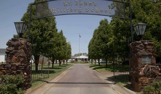 """FILE - This June 27, 2012 file photo shows the entrance to St. Johns Military Academy in Salina, Kan. The embattled Kansas military school has announced it will close after this school year, saying it has unfairly become a target for litigation and the media. St. John's Military School said Wednesday, Feb. 6, 2019, that recent legal issues and low enrollment resulting from """"negative and unfair portrayals in the media"""" created a deficit it couldn't overcome. An arbitrator recently found the school failed to supervise cadets and inflicted emotional distress in the case of a bullied 11-year-old boy. (AP Photo/Orlin Wagner, File)"""