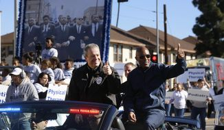 FILE - In this Jan. 21, 2019, file photo, Los Angeles, Chief of Police Michel Moore, left, and Police Commissioner, Dale Bonner ride a convertible patrol car along Martin Luther King Jr. Boulevard during the 34th annual Kingdom Day parade in Los Angeles. Moore said Thursday, Feb. 7, he hopes a newspaper report that a special police unit is pulling over a disproportionate number of African-American motorists sparks a broader conversation about how best to interpret the data. (AP Photo/Damian Dovarganes, File)