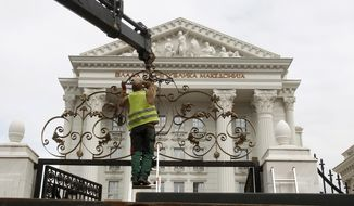 Workers dismantle metal fencing from the front of the Macedonia's Government in the capital Skopje, Thursday, Feb. 7, 2019. Dozens of workers have started dismantling the metal fence around the Macedonian government buildings, seen as symbolic move to eradicate divisions in the country and to devalue former conservative government extravaganza.  (AP Photo/Boris Grdanoski)