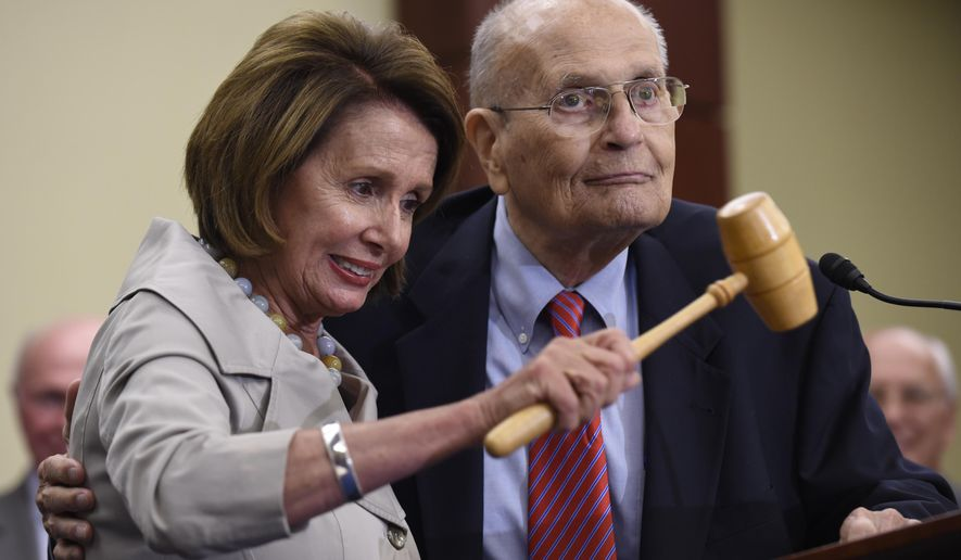 FILE - In this July 29, 2015 file photo, House Minority Leader Nancy Pelosi of Calif., standing with former Rep. John Dingell, D-Mich., holds up the gavel Dingell used 50 years ago when Medicare legislation was passed during an event marking the 50th Anniversary of Medicare and Medicaid on Capitol Hill in Washington. Dingell, the longest-serving member of Congress in American history who mastered legislative deal-making and was fiercely protective of Detroit's auto industry, has died at age 92. Dingell, who served in the U.S. House for 59 years before retiring in 2014, died Thursday, Feb. 7, 2019, at his home in Dearborn, said his wife, Congresswoman Debbie Dingell. (AP Photo/Susan Walsh, File)