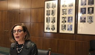 Oregon Gov. Kate Brown speaks to reporters in front of pictures of previous state governors in Salem, Ore., Thursday, Feb. 7, 2019.  Gov. Brown weighed in on the political crisis in Virginia, saying her counterpart there should step down and that the problem of whites going in blackface is due in part to a lack of awareness and stupidity. (AP Photo/Andrew Selsky)