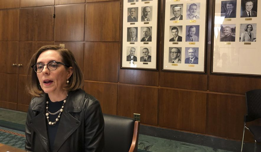 In this file photo, Oregon Gov. Kate Brown speaks to reporters in front of pictures of previous state governors in Salem, Ore., Thursday, Feb. 7, 2019. (AP Photo/Andrew Selsky) **FILE**