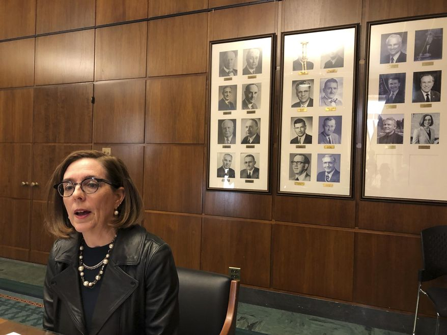 Oregon Gov. Kate Brown speaks to reporters in front of pictures of previous state governors in Salem, Ore., Thursday, Feb. 7, 2019. (AP Photo/Andrew Selsky) **FILE**