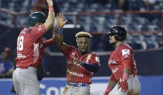 Jilton Calderon, center, Jonathan Galvez, left, and Allen Cordoba, right, of Panama's Los Toros de Herrera, celebrate on home plate after scoring runs against Puerto Rico's Cangrejeros de Santurce during the Caribbean Series baseball tournament at Rod Carew stadium in Panama City, Wednesday, Feb. 6, 2019. (AP Photo/Arnulfo Franco)