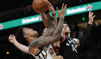 Atlanta Hawks forward John Collins (20) and Toronto Raptors guard Danny Green (14) battle for a rebound during the first half of an NBA basketball Thursday, Feb. 7, 2019, in Atlanta. (AP Photo/John Bazemore)