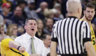 San Francisco head coach Kyle Smith, left, speaks with an official during the first half of an NCAA college basketball game against Gonzaga in Spokane, Wash., Thursday, Feb. 7, 2019. (AP Photo/Young Kwak)