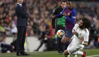 Real defender Marcelo, right, duels for the ball with Barcelona defender Nelson Semedo during the Copa del Rey semifinal first leg soccer match between FC Barcelona and Real Madrid at the Camp Nou stadium in Barcelona, Spain, Wednesday Feb. 6, 2019. (AP Photo/Manu Fernandez)