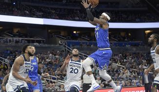 Orlando Magic guard Terrence Ross (31) goes up for a shot between Minnesota Timberwolves center Karl-Anthony Towns (32), guard Josh Okogie (20) and forward Andrew Wiggins (22) during the second half of an NBA basketball game Thursday, Feb. 7, 2019, in Orlando, Fla. (AP Photo/Phelan M. Ebenhack)