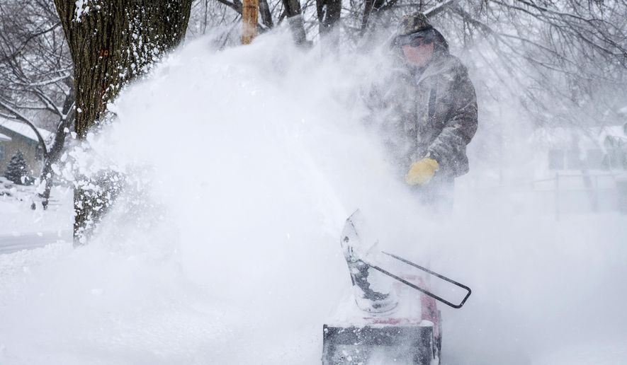 Kip Cartney is engulfed in blowing snow as he clears the sidewalk near his home as snow falls Thursday, Feb. 7, 2019, in Rochester, Minn. (Joe Ahlquist/The Rochester Post-Bulletin via AP)