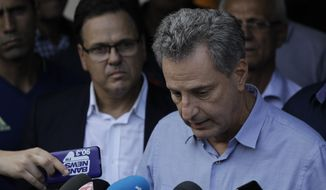 The president of the Flamengo soccer club Rodrigo Landim, right, talks to the press after a deadly fire at the soccer club in Rio de Janeiro, Brazil, Friday, Feb. 8, 2019. A fire tore through the sleeping quarters of the Flamengo soccer club development league, one of Brazil's most popular professional soccer clubs, killing several people who were most likely players and injuring others, authorities said. (AP Photo/Leo Correa)