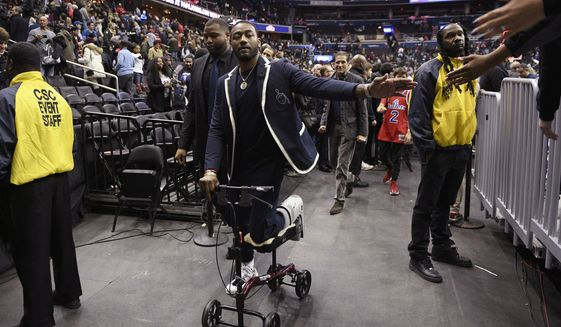 Washington Wizards guard John Wall greets fans after the team's NBA basketball game against the Cleveland Cavaliers, Friday, Feb. 8, 2019, in Washington. The Wizards won 119-106. (AP Photo/Nick Wass)
