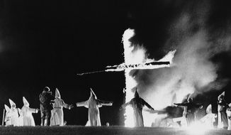 In this Sept. 27, 1987, file photo, the Invisible Empire, Ku Klux Klan members wearing traditional robes form a circle around a burning cross in Rumford, Maine. (AP Photo/Scott Perry, File)