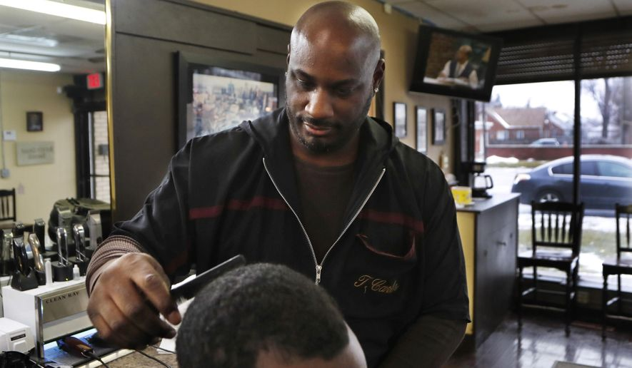 """In this Thursday, Feb. 7, 2019 photo, barber Thomas Carter cuts a customer's hair in Detroit. Carter says there's nothing funny about blackface, calling it a """"huge form of disrespect"""" to African Americans. Past uses of blackface as attempts to humor have clouded the political futures of two of Virginia's top leaders, while angering many African Americans who see it as part of America's painful history of racism, hate and exploitation. (AP Photo/Carlos Osorio)"""