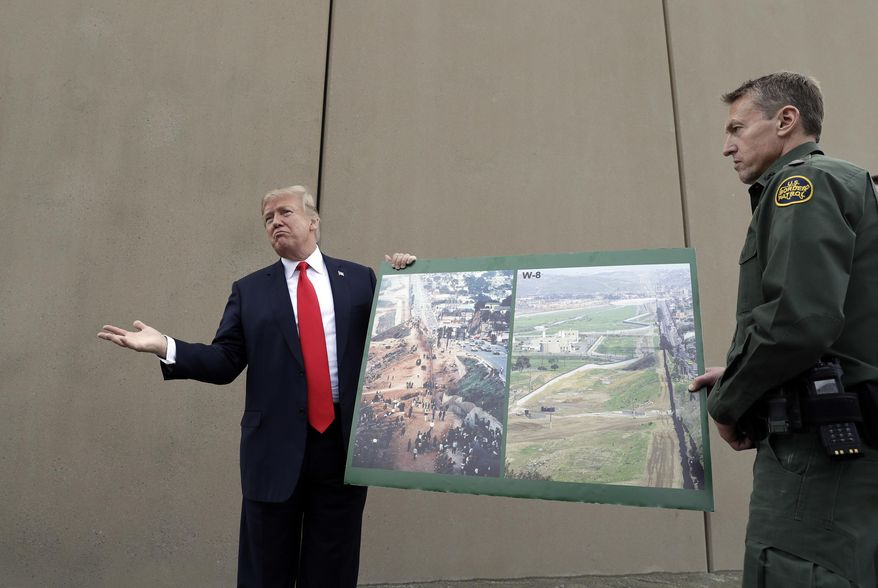 In this Tuesday, March 13, 2018, photo, President Donald Trump holds a poster with photographs of the U.S. - Mexico border area as he reviews border wall prototypes in San Diego with Rodney Scott, the U.S. Border Patrol's San Diego sector chief. The Trump administration said Thursday, Feb. 7, 2019, it would waive environmental reviews to replace up to 14 miles (22.5 kilometers) of border barrier in San Diego, shielding itself from potentially crippling delays. (AP Photo/Evan Vucci) **FILE**