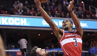 Washington Wizards guard Bradley Beal (3) goes to the basket against Cleveland Cavaliers forward Kevin Love (0) during the first half of an NBA basketball game Friday, Feb. 8, 2019, in Washington. Love was called for a foul on the play. (AP Photo/Nick Wass)