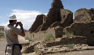FILE - In this Aug. 10, 2005, file photo, tourist Chris Farthing from Suffolks County, England, takes a picture while visiting Chaco Culture National Historical Park in northwestern New Mexico. U.S. land managers no longer plan to move forward in March with the sale of oil and gas leases that include land near Chaco Culture National Historical Park. The decision Friday, Feb. 8, 2019, by the federal Bureau of Land Management comes after tribal leaders and others criticized the agency for pushing ahead with drilling permit reviews and preparations for energy leases near the site. (AP Photo/Jeff Geissler, File)