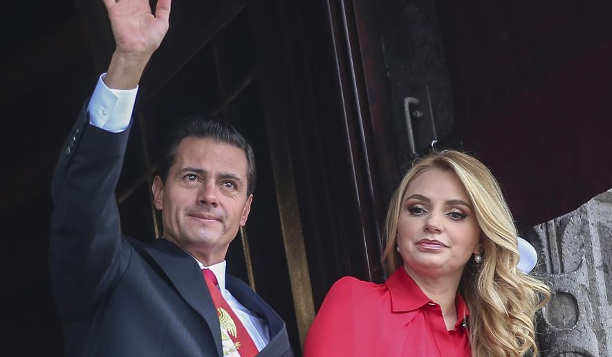 FILE - In this Sept. 16, 2018 file photo, Mexico's President Enrique Pena Nieto waves from a National Palace balcony, accompanied by first lady Angelica Rivera, during the Independence Day military parade in the Zocalo of Mexico City. Rivera posted on her Instagram account on Friday, Feb. 8, 2019, that she is divorcing Pena Nieto. (AP Photo/Anthony Vazquez, File)