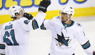 San Jose Sharks' Evander Kane, right, celebrates his goal against the Calgary Flames with teammate Justin Braun during the first period of an NHL hockey game Thursday, Feb. 7, 2019, in Calgary, Alberta. (Larry MacDougal/The Canadian Press via AP)