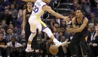 Phoenix Suns guard Elie Okobo, right, passes underneath a jumping Golden State Warriors guard Stephen Curry (30) during the first half of an NBA basketball game Friday, Feb. 8, 2019, in Phoenix. (AP Photo/Ross D. Franklin)