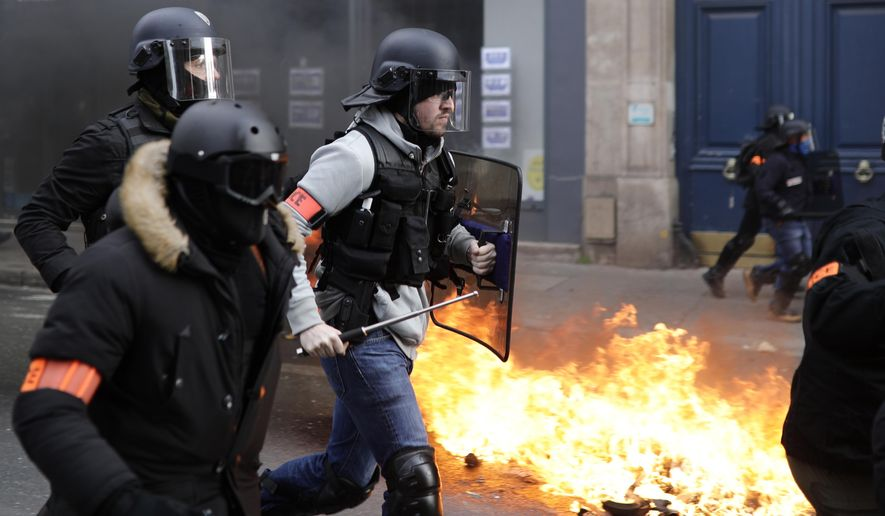Riot police run past burning dustbins set on fire by yellow vest protesters as they keep pressure on French President Emmanuel Macron's government, for the 13th straight weekend of demonstrations, in Paris, France, Saturday, Feb. 9, 2019. (AP Photo/Kamil Zihnioglu)