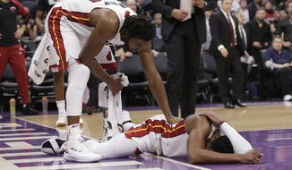 Miami Heat forward Justise Winslow, left, checks on teammate Dwyane Wade, who hit his head after a hard landing during the first quarter of the team's NBA basketball game against the Sacramento Kings. Friday, Feb. 8, 2019, in Sacramento, Calif. (AP Photo/Rich Pedroncelli)