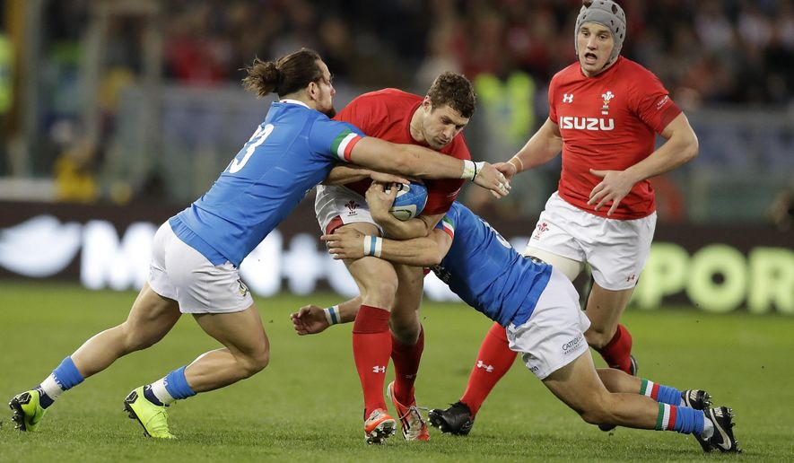 Wales' Jake Ball, center, is tackled by Italy's Michele Campagnaro, left, and Italy's Guglielmo Palazzani during the Six Nations rugby union international between Italy and Wales, at Rome's Olympic Stadium, Saturday, Feb. 9, 2019. (AP Photo/Andrew Medichini)