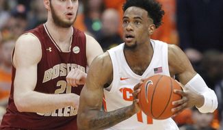 Syracuse's Oshae Brissett, right, looks to pass the ball while being guarded by Boston College's Nik Popovic, left, during the second half of an NCAA college basketball game in Syracuse, N.Y., Saturday, Feb. 9, 2019. Syracuse won 67-56. (AP Photo/Nick Lisi)