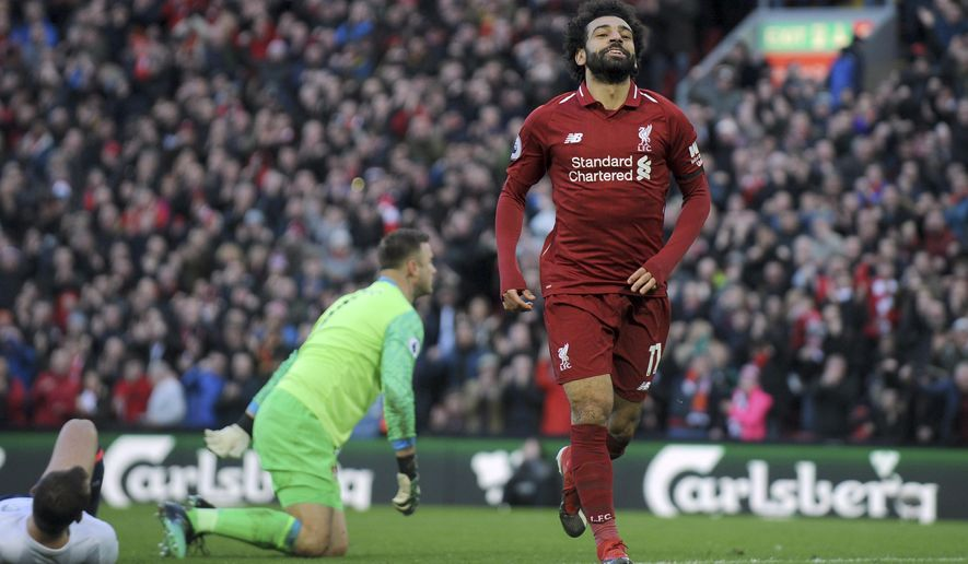 Liverpool's Mohamed Salah celebrates after scoring his side's third goal during the English Premier League soccer match between Liverpool and AFC Bournemouth at Anfield stadium in Liverpool, England, Saturday, Feb. 9, 2019. (AP Photo/Rui Vieira)
