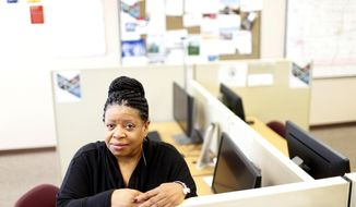 In this Feb. 1, 2019, photo, Debra Hodges-Harmon sits at a desk at the Cedar Valley Iowa Works in Waterloo, Iowa. The Waterloo-Cedar Falls metro area is grappling with an article published in November that listed it as the No. 1 worst metro area in the U.S. to be African-American.  (Brandon Pollock/The Courier via AP)