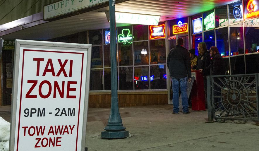 In this Friday, Jan. 25, 2019 photo, a Taxi Zone sign is displayed in front of a bar in Lincoln, Neb. Taxi Zone allow ride sharing vehicles to pull over safely while dropping passengers off in front of popular bars. (Savannah Blake/Lincoln Journal Star via AP)