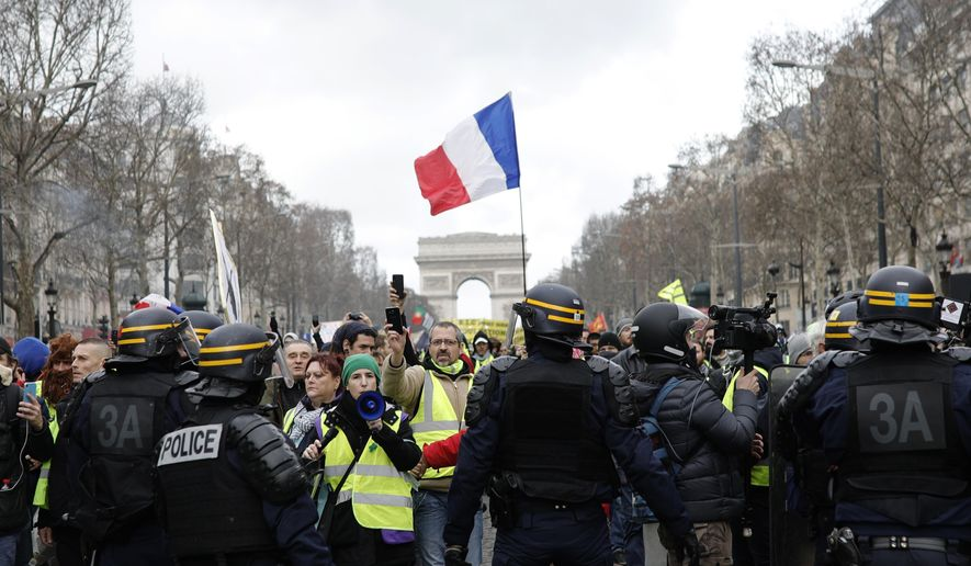 Yellow vest protesters walk down the famed Champs Elysees avenue to keep pressure on French President Emmanuel Macron's government, for the 13th straight weekend of demonstrations, in Paris, France, Saturday, Feb. 9, 2019. (AP Photo/Kamil Zihnioglu)