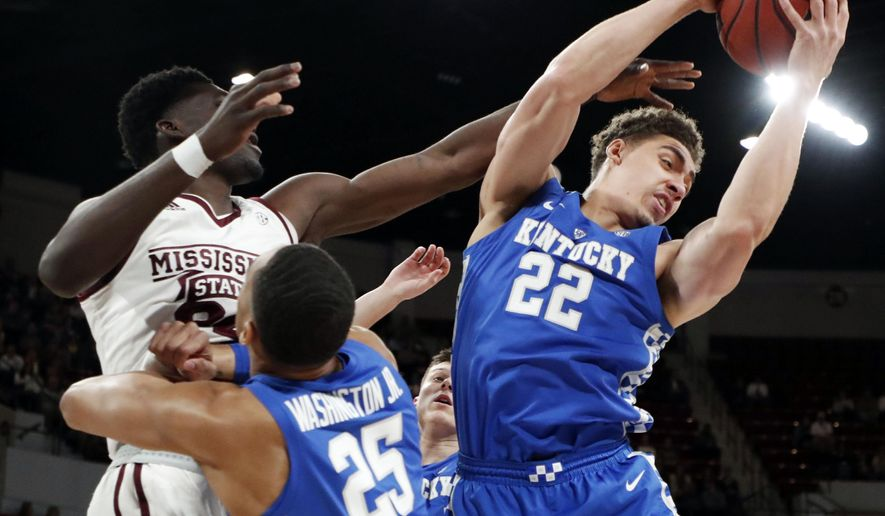 Kentucky forward Reid Travis (22) pulls down a rebound while forward PJ Washington (25) pushes back on a Mississippi State player during the first half of an NCAA basketball game in Starkville, Miss., Saturday, Feb. 9, 2019. (AP Photo/Rogelio V. Solis)