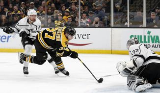 Boston Bruins' Patrice Bergeron is tripped up by Los Angeles Kings' Ilya Kovalchuk as he moves in on goaltender Jonathan Quick during the second period of an NHL hockey game Saturday, Feb. 9, 2019, in Boston. (AP Photo/Winslow Townson)