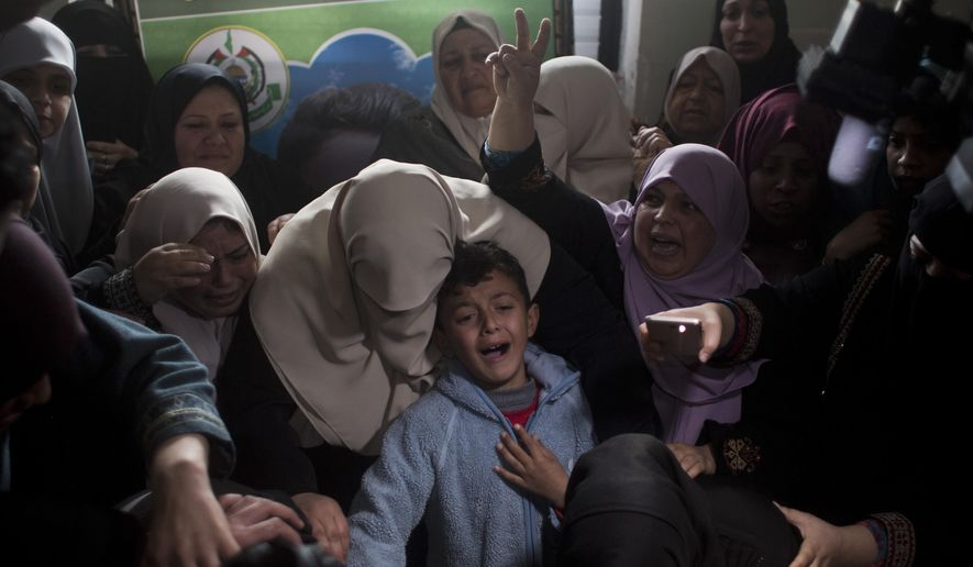 Relatives of Palestinian teenager Hassan Shalabi, 14, mourn over his body at the family home during his funeral in Nuseirat refugee camp, central Gaza Strip, Saturday, Feb 9, 2019. Israeli troops shot and killed two Palestinian teenagers Friday as thousands held demonstrations along the perimeter fence separating Gaza and Israel. (AP Photo/Khalil Hamra)