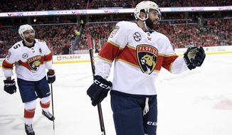 Florida Panthers defenseman Keith Yandle, right, reacts as he heads to the bench to celebrate his goal during the first period of an NHL hockey game against the Washington Capitals, Saturday, Feb. 9, 2019, in Washington. Also seen is defenseman Panthers Aaron Ekblad (5). (AP Photo/Nick Wass)