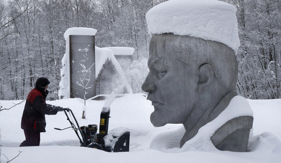 A worker uses a snowblower to clear the area around a statue of Soviet Union founder Vladimir Lenin at the Lenin Hut Museum in a forest near Razliv Lake, outside St. Petersburg, Russia, Monday, Feb. 4, 2019. Another cyclone caused a week of snowfall in St. Petersburg. (AP Photo/Dmitri Lovetsky)