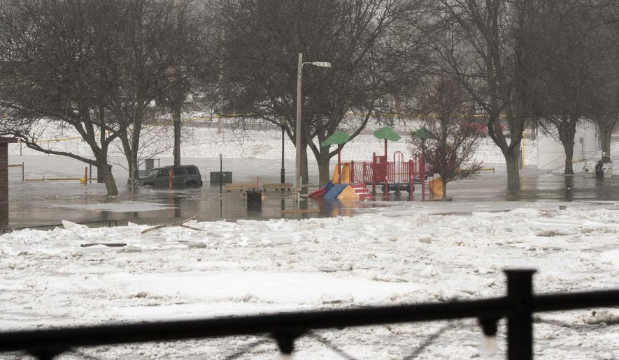 A car is stuck in the street on Water Street in downtown Portland, Mich., Friday, Fe. 8, 2019, near Grand River Ave. The Grand River is flooding and causing some evacuations. (Michael Dae Smith/Lansing State Journal via AP)