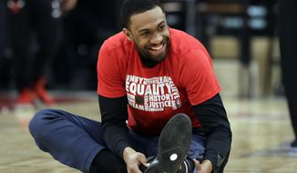 Washington Wizards forward Jabari Parker smiles as he stretches before an NBA basketball game against the Chicago Bulls, Saturday, Feb. 9, 2019, in Chicago. (AP Photo/Nam Y. Huh)