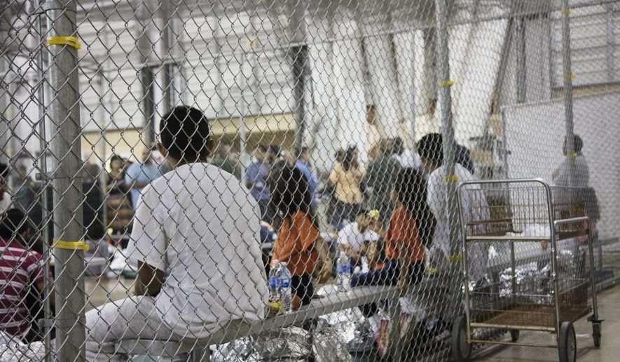 In this June 17, 2018, file photo provided by U.S. Customs and Border Protection, people who've been taken into custody related to cases of illegal entry into the United States, sit in one of the cages at a facility in McAllen, Texas. Records obtained by The Associated Press highlight some of the problems that plague government facilities for immigrant youth. (U.S. Customs and Border Protection's Rio Grande Valley Sector via AP) ** FILE **