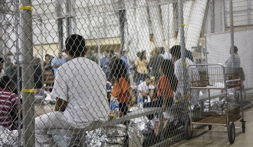 In this June 17, 2018, file photo provided by U.S. Customs and Border Protection, people who've been taken into custody related to cases of illegal entry into the United States, sit in one of the cages at a facility in McAllen, Texas. Records obtained by The Associated Press highlight some of the problems that plague government facilities for immigrant youth. (U.S. Customs and Border Protection's Rio Grande Valley Sector via AP)