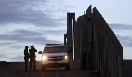 In this Wednesday, Nov. 21, 2018, file photo, United States Border Patrol agents stand by a vehicle near one of the border walls separating Tijuana, Mexico, and San Diego. (AP Photo/Gregory Bull, File)