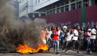 Demonstrators run away during a protest to demand the resignation of President Jovenel Moise and demanding to know how Petro Caribe funds have been used by the current and past administrations, in Port-au-Prince, Haiti, Saturday, Feb. 9, 2019. Much of the financial support to help Haiti rebuild after the 2010 earthquake comes from Venezuela's Petro Caribe fund, a 2005 pact that gives suppliers below-market financing for oil and is under the control of the central government. (AP Photo/Dieu Nalio Chery)