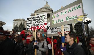 In this Wednesday, Jan. 30, 2019, file photo, teachers from the Denver Public Schools carry placards as they wait to march after a rally in support of a strike outside the State Capitol in Denver. Denver teachers are planning to strike Monday, Feb. 11, 2019, after failed negotiations with the school district over base pay. (AP Photo/David Zalubowski, File)