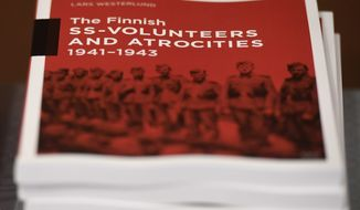 The research document entitled The Finnish SS-volunteers and atrocities 1941 - 1943 against Jews, detailing atrocities against civilians and Prisoners of War in Ukraine and the Caucasus Region, pictured in Helsinki, Finland, on Friday Feb. 8, 2019.  Senior Israeli Holocaust historian, Efraim Zuroff of the Simon Wiesenthal Center, on Sunday Feb. 10, 2019, has praised Finnish authorities for publishing a report concluding that the Nordic country's volunteer battalion serving with Nazi Germany's notorious Waffen-SS took part in atrocities during World War II including participating in the mass murder of Jews.(Heikki Saukkomaa/Lehtikuva via AP)